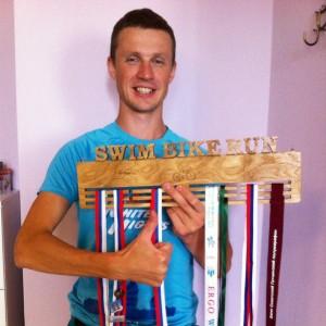 Триатлет Алексей Лукашин с держателем для медалей Swim Bike Run